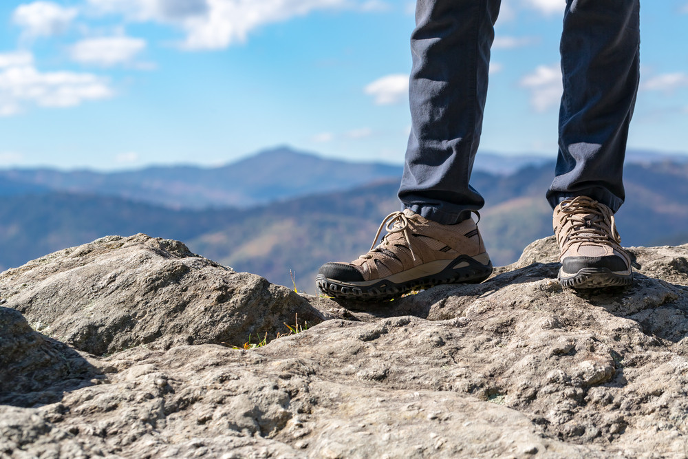 Man standing on the edge of a cliff high above the mountains below