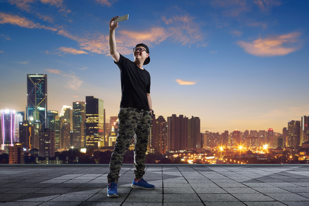 man taking selfie at rooftop on city skyline background