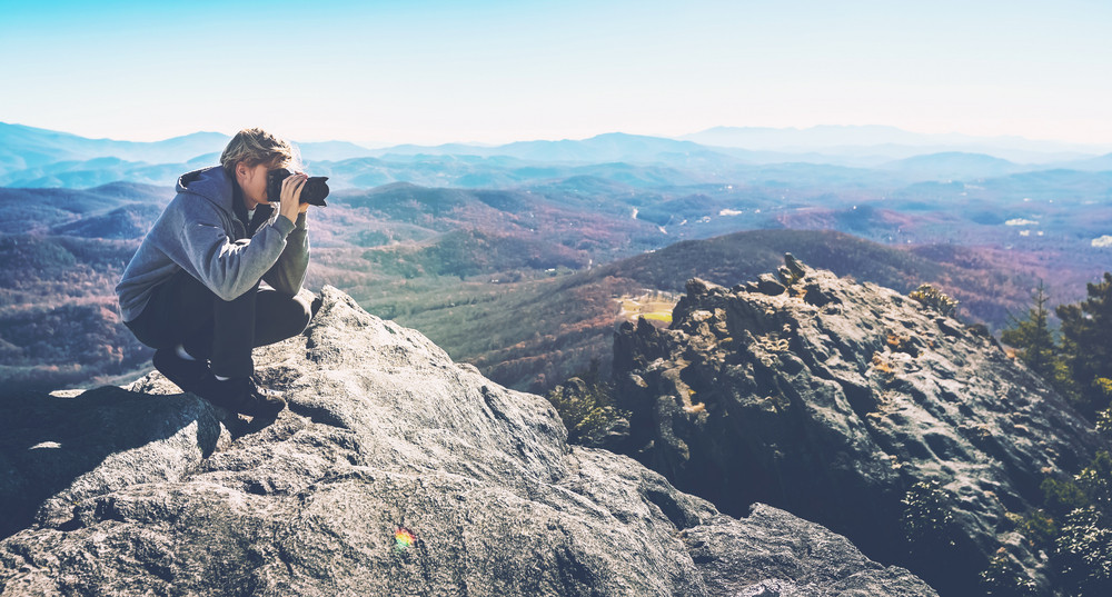 Man with a camera on top of a cliff overlooking the mountains