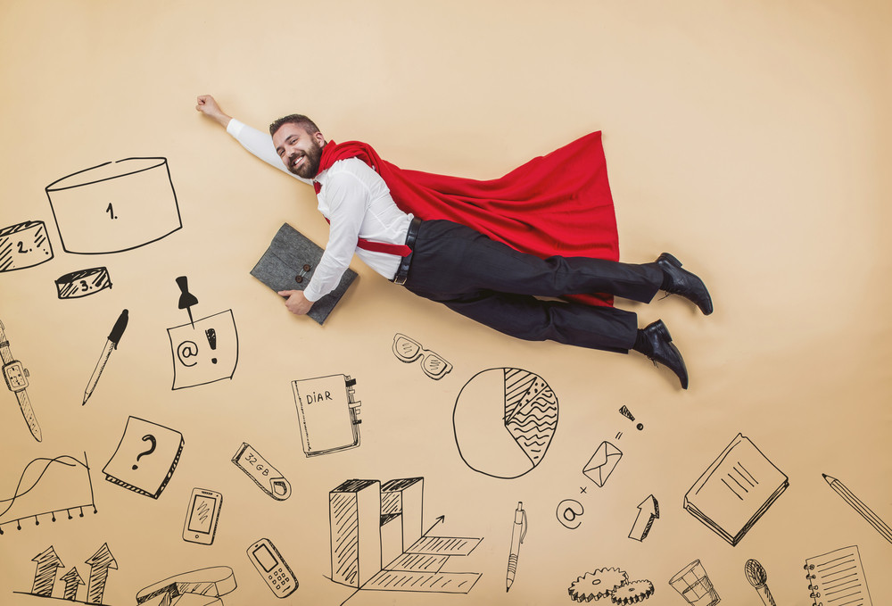 Manager in a super hero pose wearing a red cloak. Studio shot on a beige background.