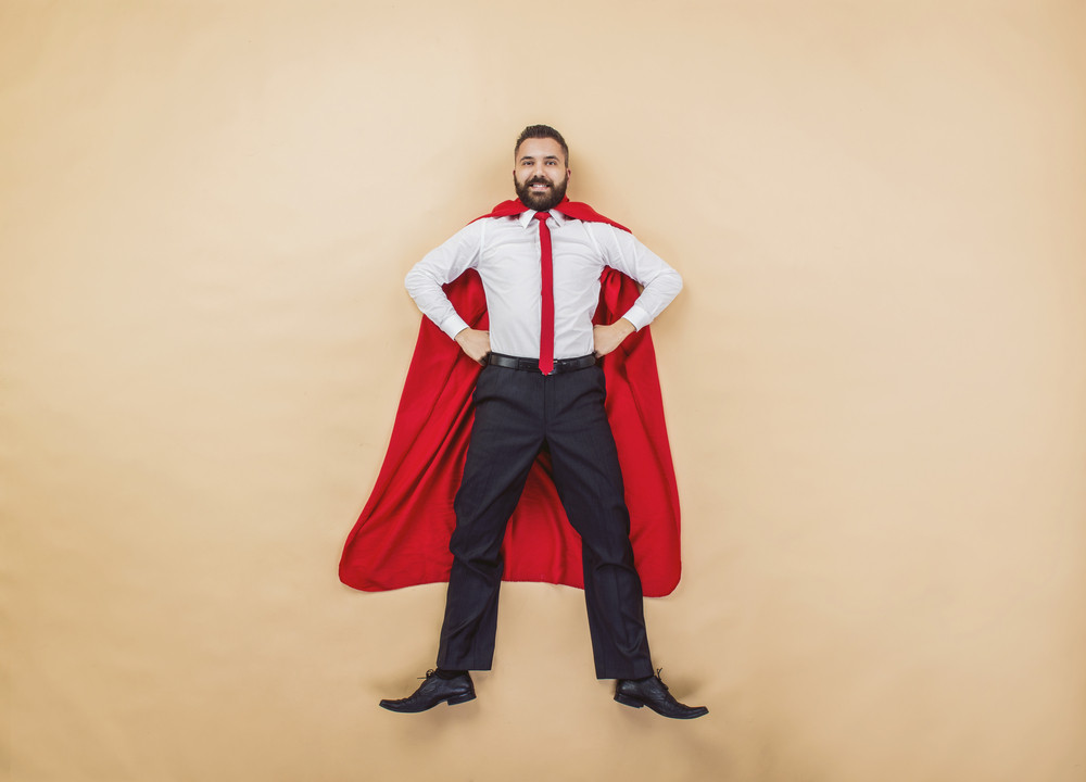 Manager wearing a red superman cloak. Studio shot on a beige background.