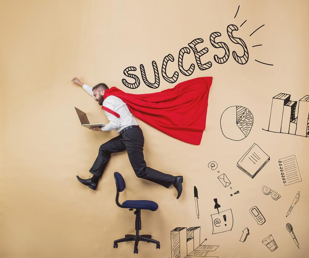 Manager wearing cloak of super hero. Studio shot on a beige background.