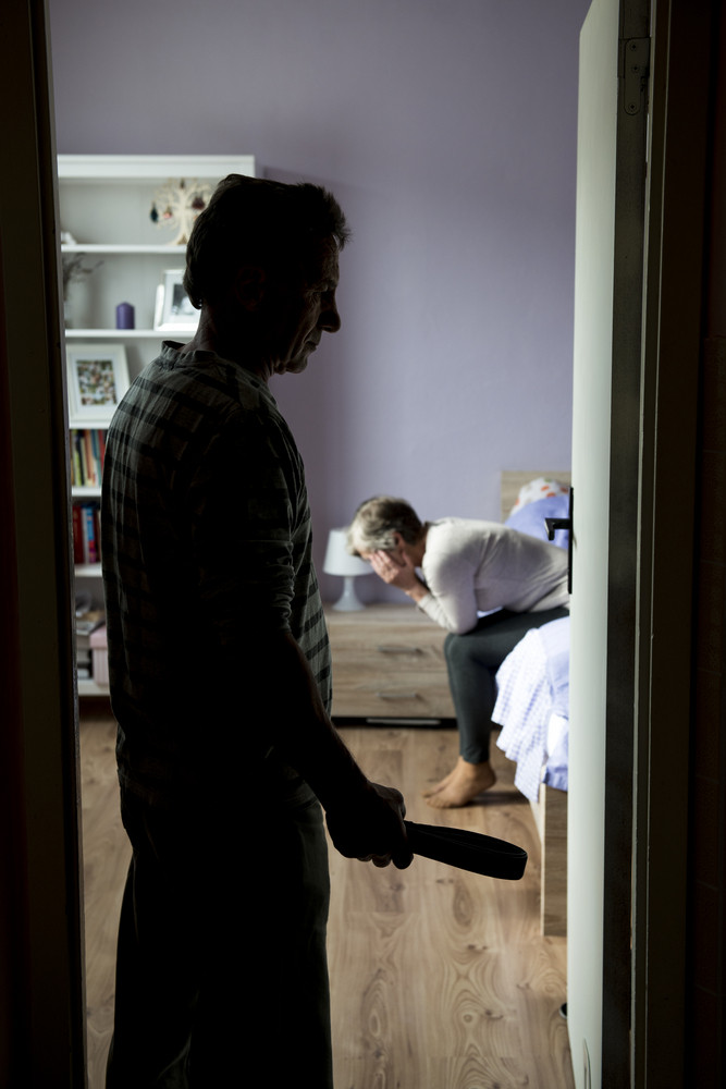 Mature woman siiting on the bed is scared of man with belt. Woman is victim of domestic violence and abuse.
