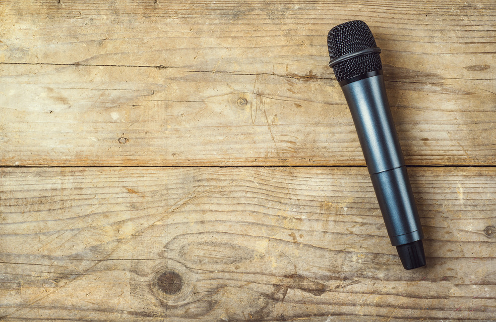 Microphone on a wooden office desk background. View from above.