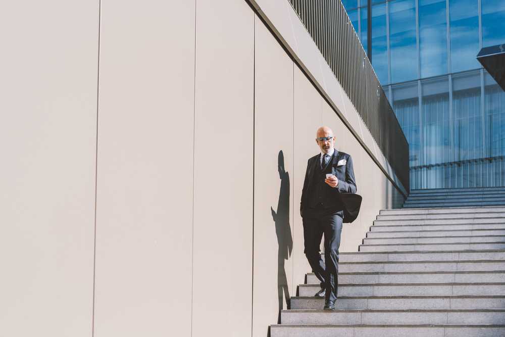 Middle-age contemporary businessman outdoor in the city, using smart phone hand hold - business, work, communication concept