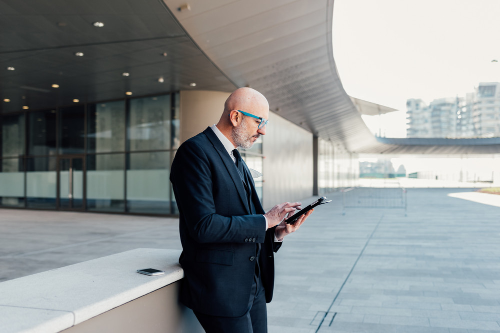 Middle age contemporary businessman outdoor in the city using tablet, looking down the screen - technology, business, communication concept