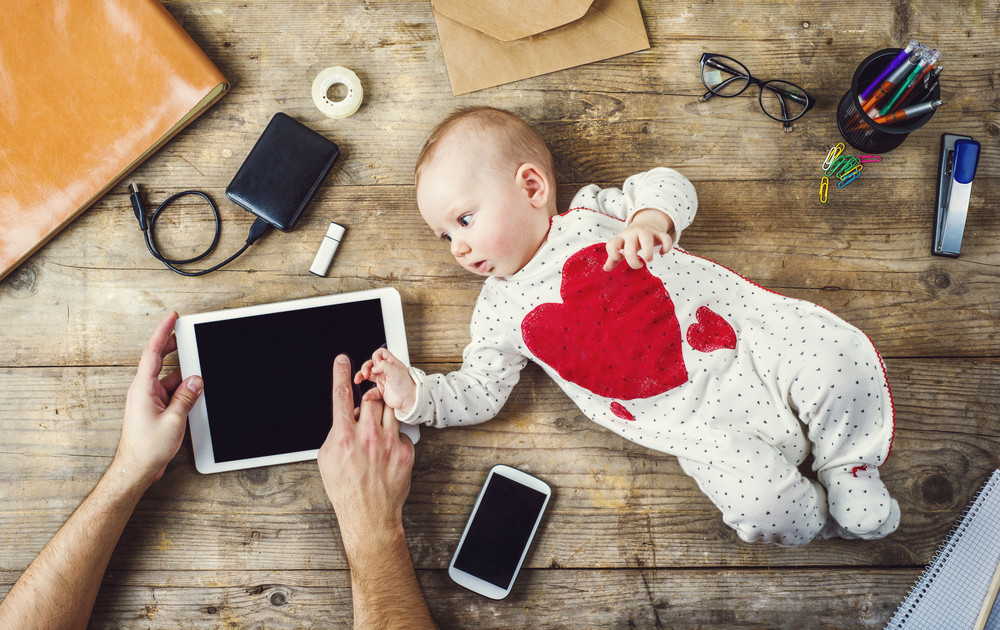 Mix of office supplies and gadgets on a wooden desk background alongside with cute little baby. View from above.