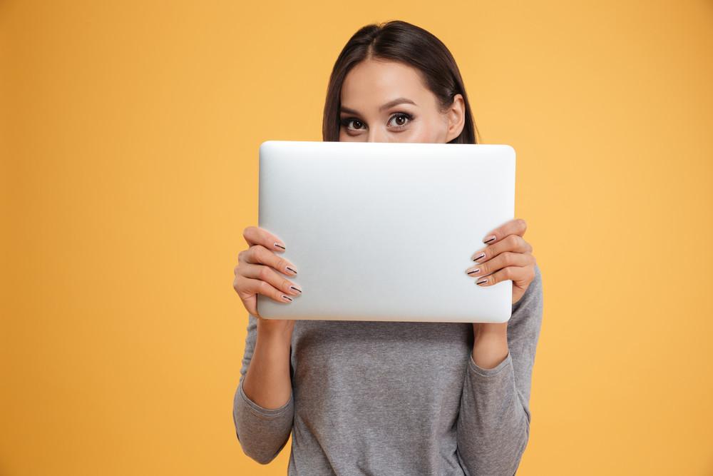 Model hiding behind laptop in studio. isolated orange background