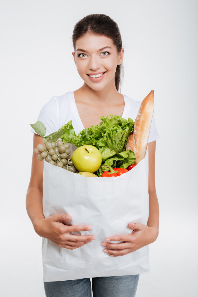 Model holding package with food in stodio and looking at camera. Vertical image. Isolated white background
