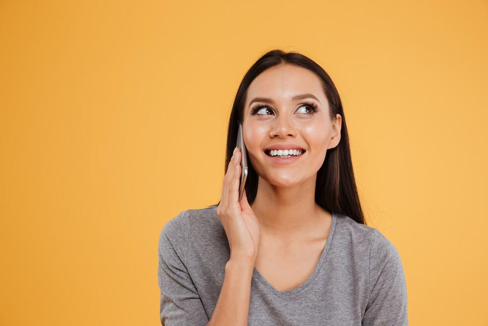 Model talking on phone. looking up. isolated orange background