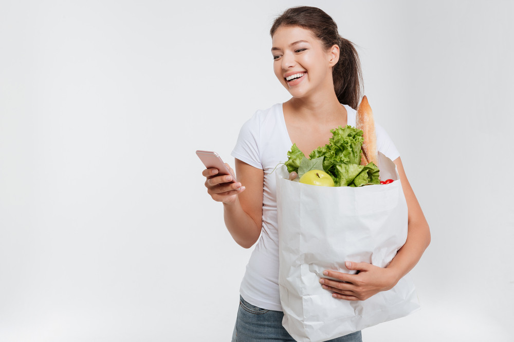 Model with food in package and phone. In studio. Isolated white background