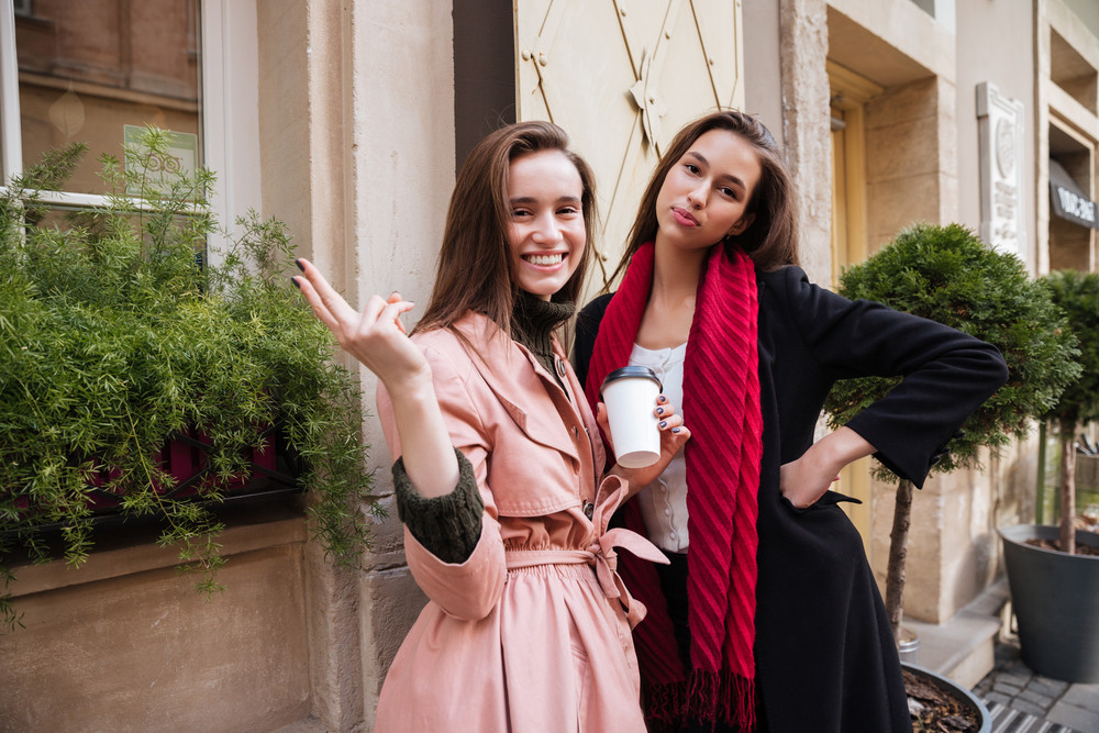 Models in coats looking at camera. on the street with coffee