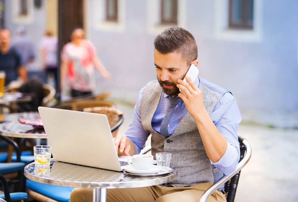 Modern hipster businessman drinking espresso coffee in the city cafe during lunch time and working on laptop and calling by mobile phone