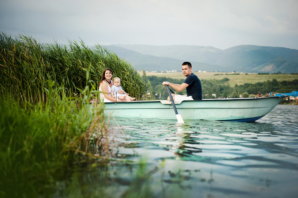 Mother and father with baby boy on boat on lake