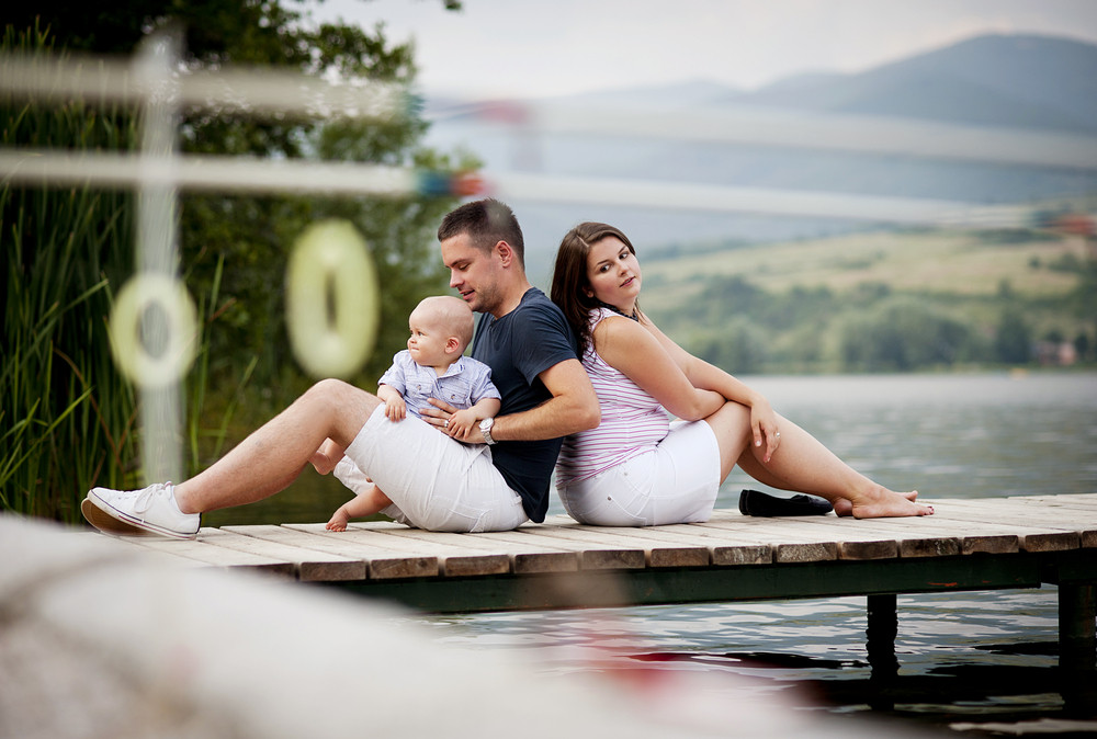 Mother and father with baby boy sitting on pier by the lake