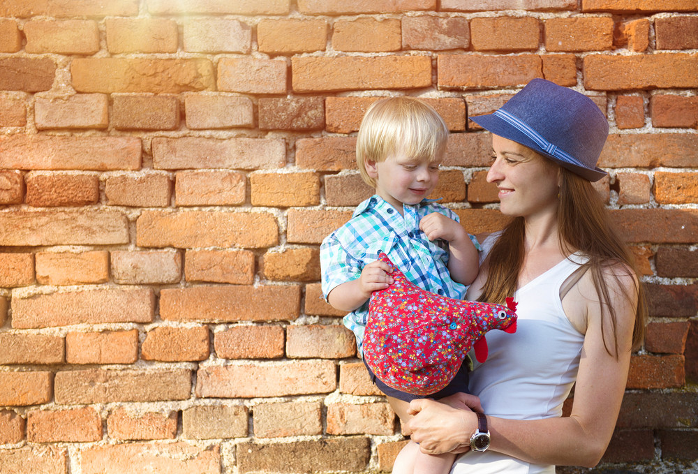 Mother and son hugging by the brick wall in countryside.