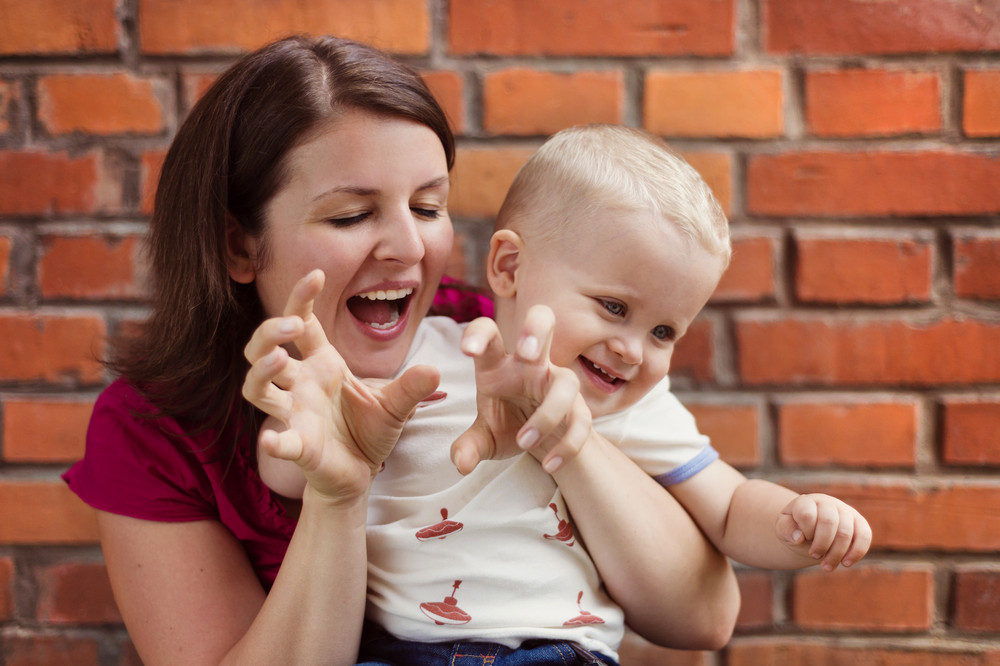 Mother and son making funny faces together on a brick wall background