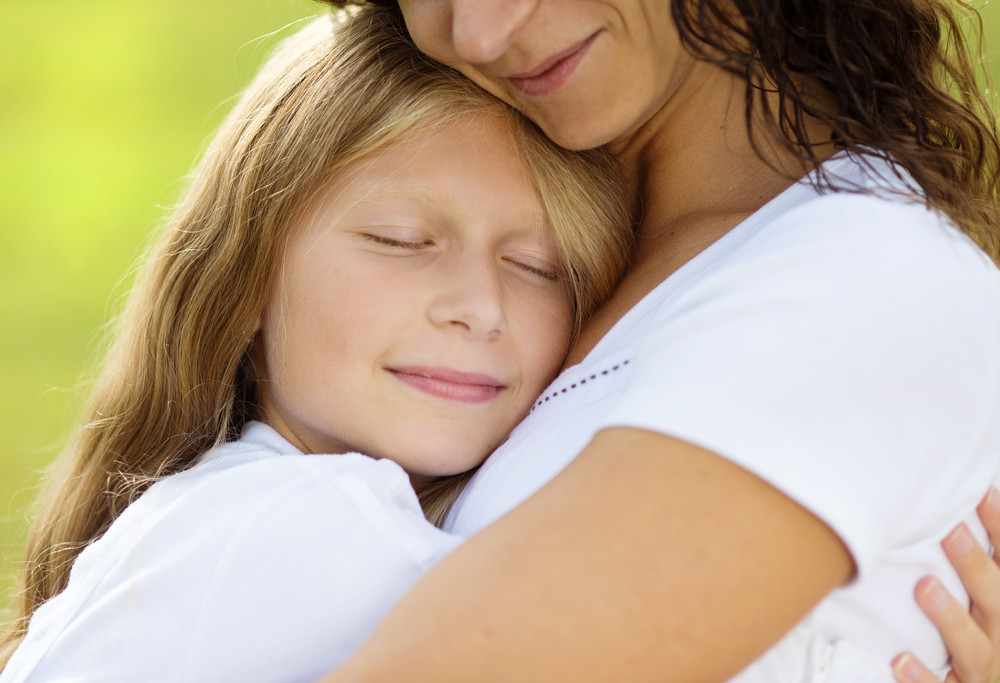 Mother and teenage daughter hugging and smiling together in summer garden.