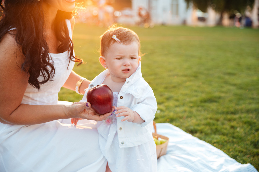 Mother giving fresh red apple to her little daughter in park