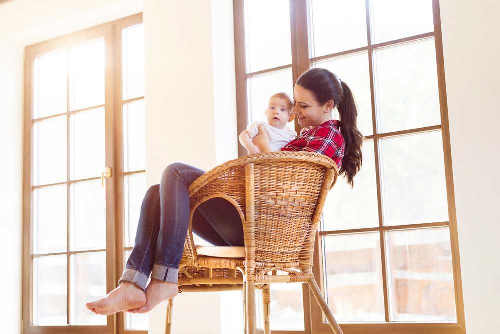 Mother sitting in a chair holding her little baby girl in her arms.