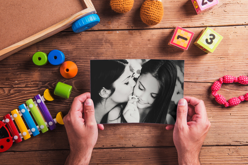 Mothers day composition. Unrecognizable man holding black-and-white picture. Various toys. Studio shot on wooden background.