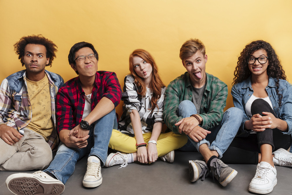 Multiethnic group of comical playful young people sitting and making funny faces over yellow background