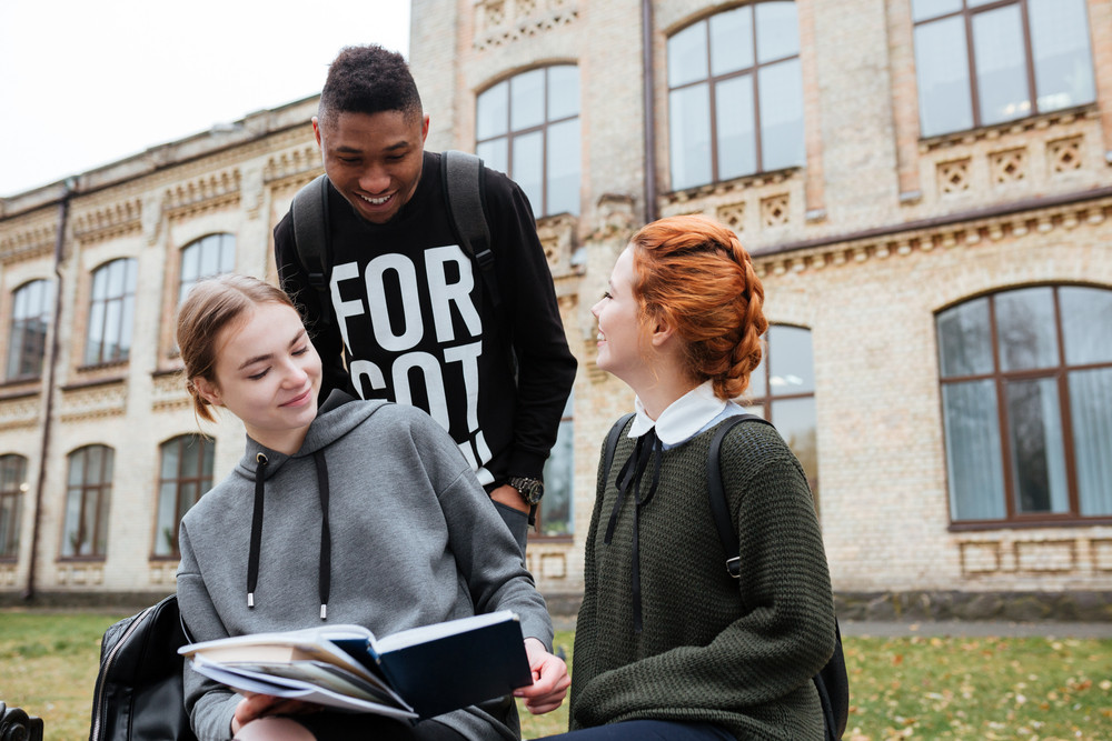 Multiethnic group of happy young people reading book and talking outdoors at the unversity campus