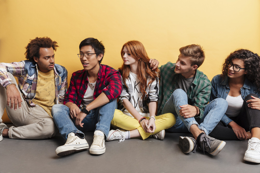 Multiethnic group of happy young people sitting listening their friend over yellow background