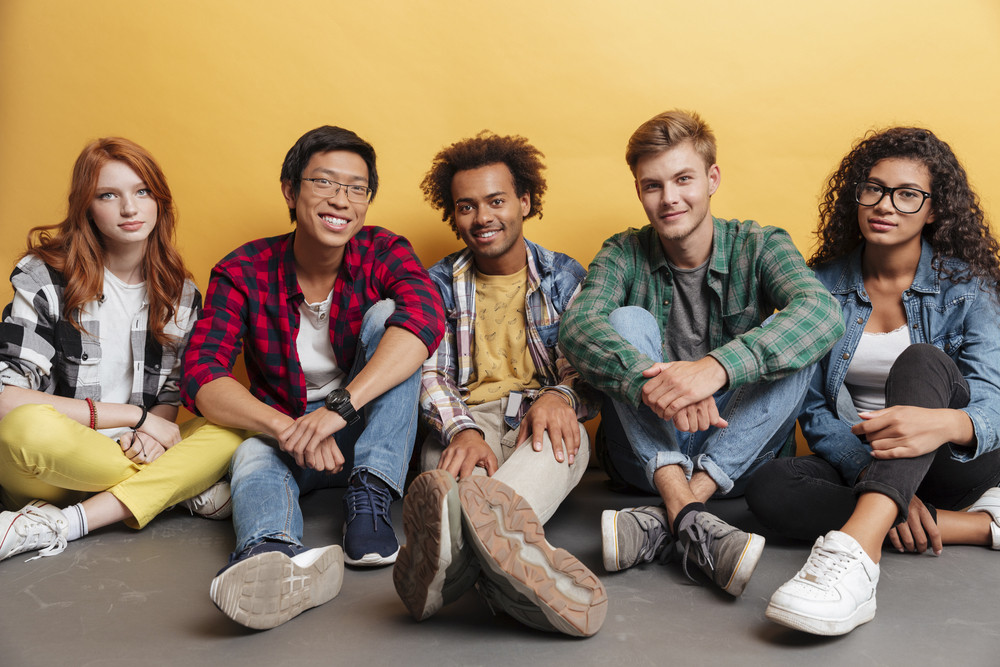 Multiethnic group of happy young people sitting together over yellow background