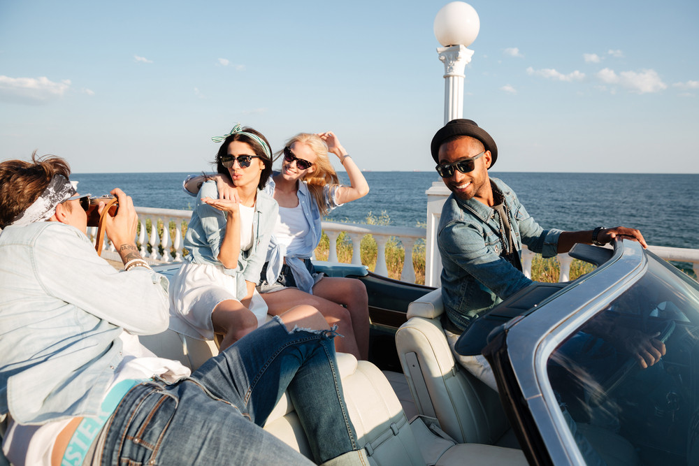 Multiethnic group of happy young people taking photos in cabriolet in summer