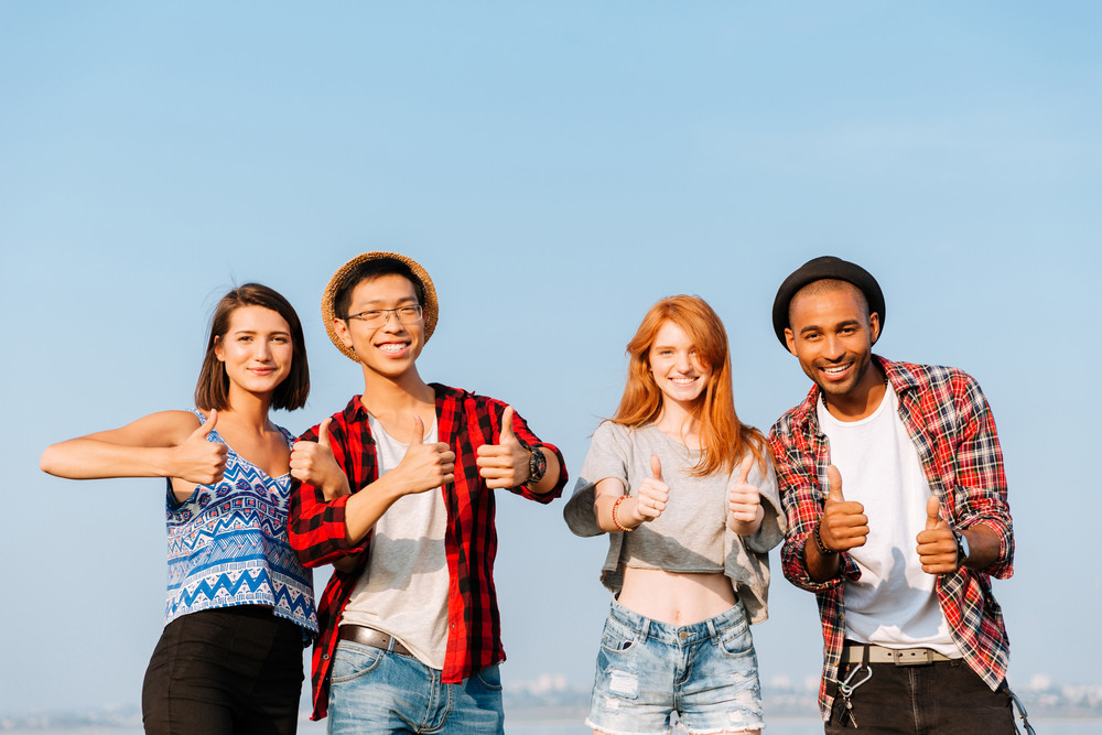 Multiethnic group of smiling young friends standing and showing thumbs up over blue sky background