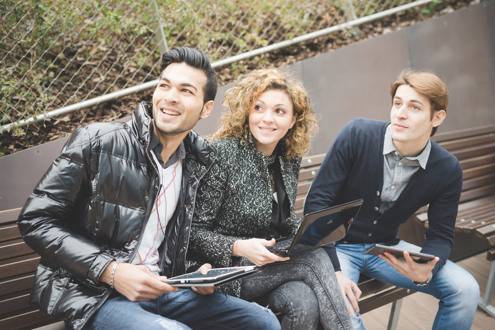 Multiracial business people working outdoor in town sitting on a bench, connected with technological devices like tablet and laptop, overlooking right, smiling - business, work, carefreeness concept