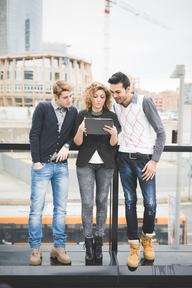 Multiracial contemporary business people working outdoor in town connected with technological devices like tablet, lokking down on the screen - finance, business, technology concept