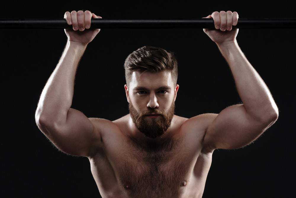 Muscular man on to horizontal bar. isolated dark background