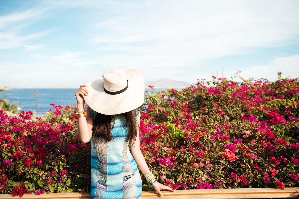 Mystery Woman in beachwear and hat with flowers on background