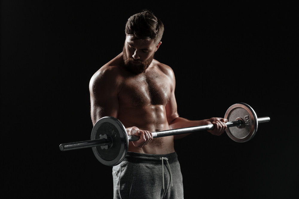 Naked muscular man with barbell. isolated dark background