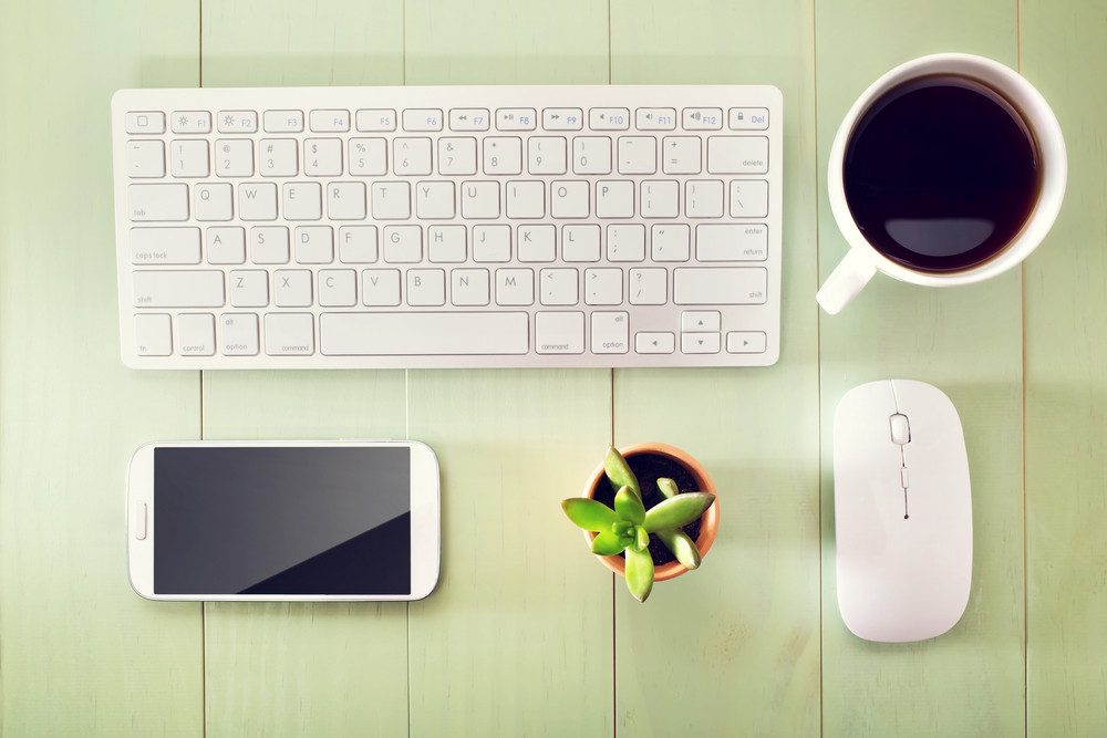 Neat workstation on a wooden desk viewed from overhead with a wireless computer mouse and keyboard, mobile phone, cup of coffee and houseplant