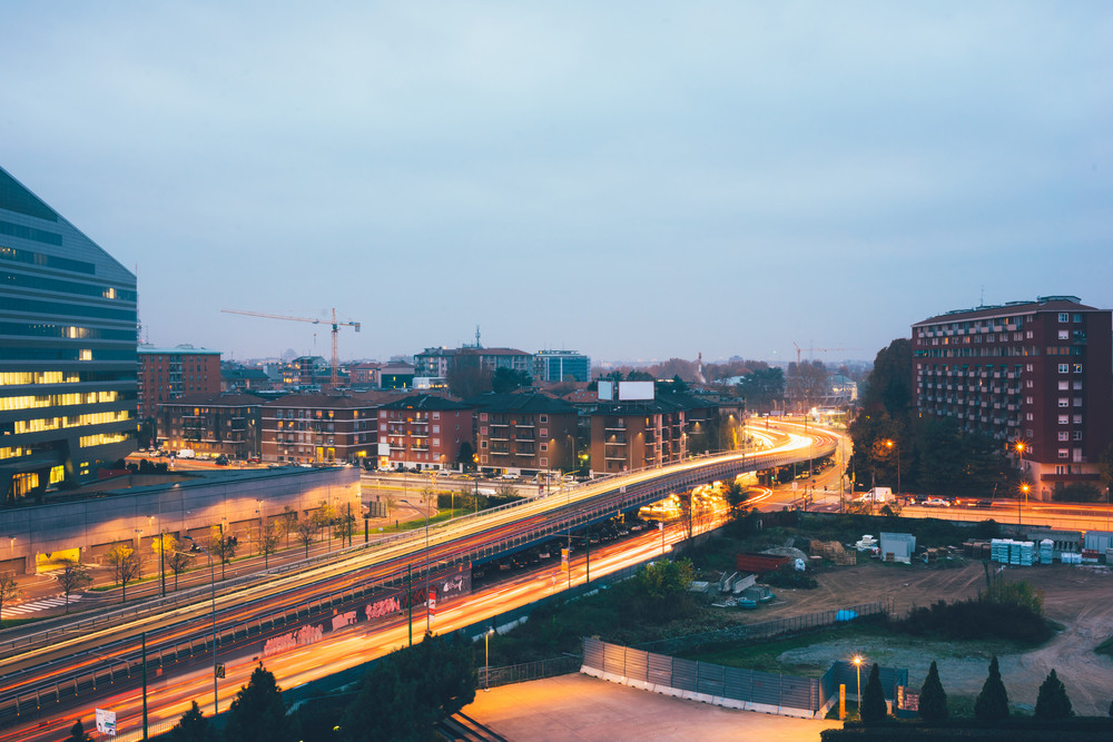 Night view long exposure cityscape with colorful trail made by cars passing by in traffic - city life, rush hour concept