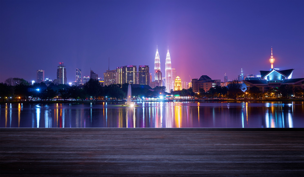 Night view of Kuala Lumpur city with stunning reflection in water and wooden board