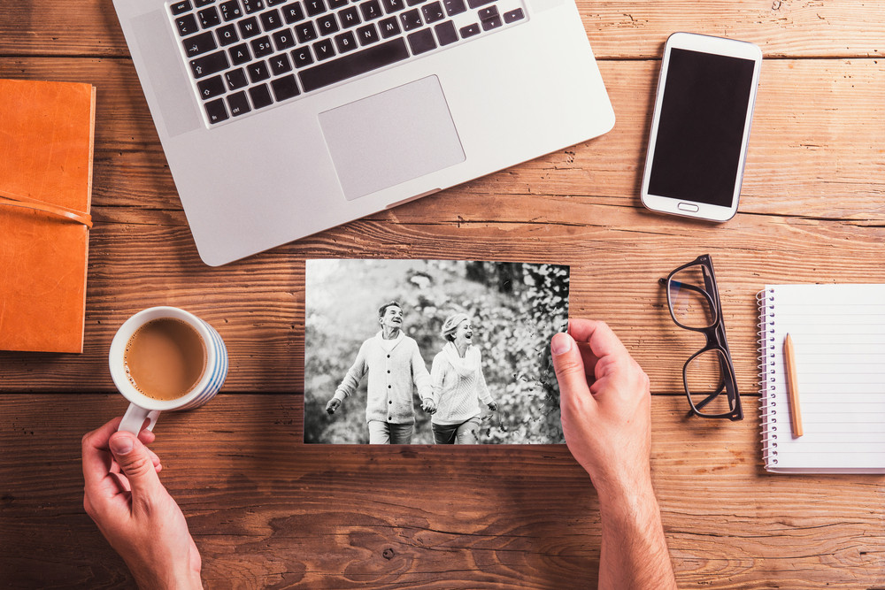Office desk with various objects. Hands of unrecognizable man holding black and white picture of senior couple in autumn nature and cup of coffee. Studio shot on wooden background.