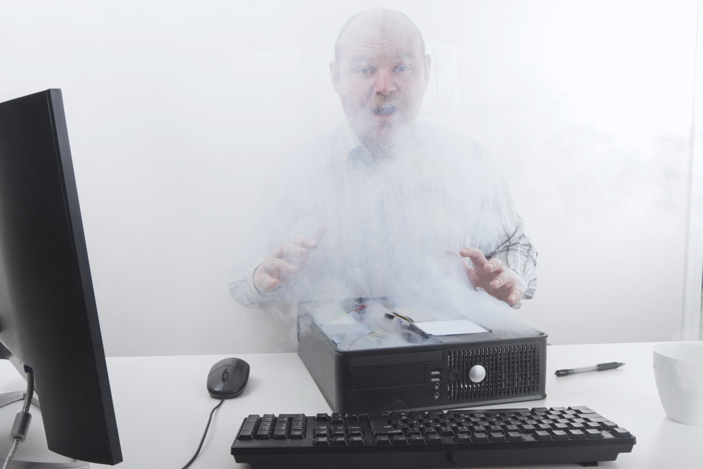 Office worker / businessman with computer problems. Smoke. time to buy a new computer?