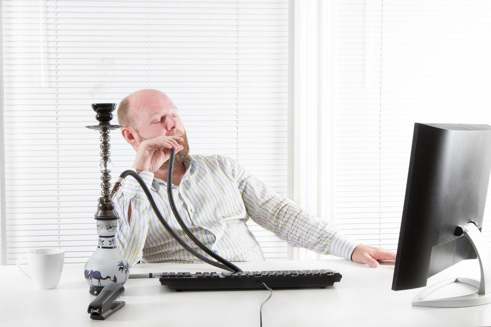 Office worker smoking water pipe in his office.