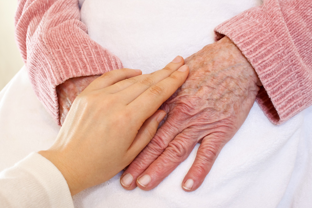 Old and young hands on white blanket