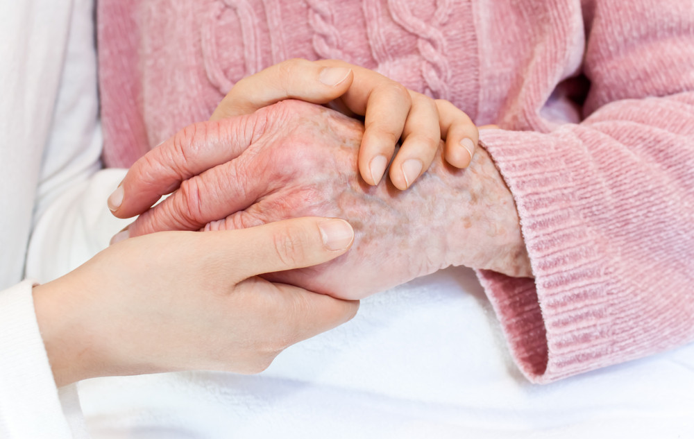 Old and young holding hands over the white blanket