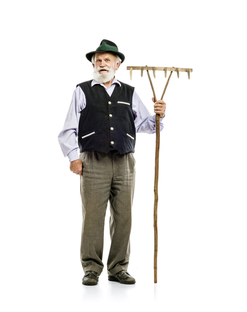 Old bearded bavarian man in hat holding rake in his hand, isolated on white background