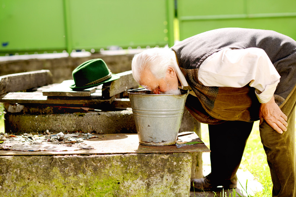 Old farmer is washing his face with water from bucket
