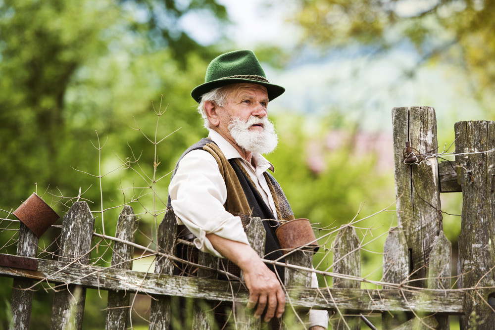Old farmer with beard and hat standing by the lath fence with empty tins on top