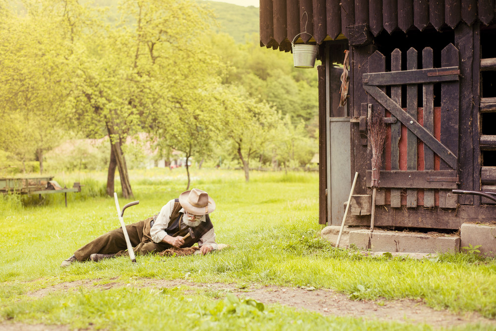 Old farmer with beard is repairing his scythe before using to mow the grass traditionally