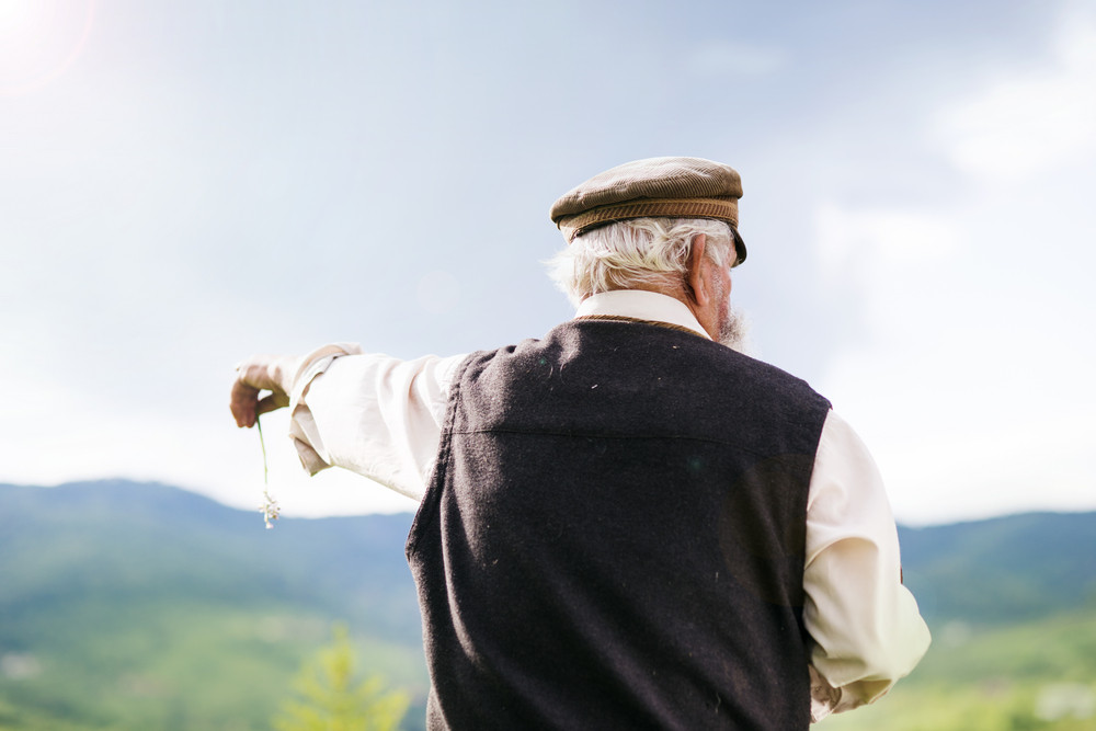 Old farmer with beard is walking in meadow