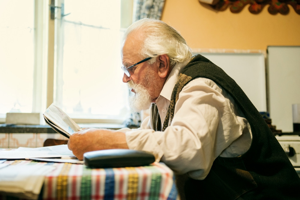 Old man reading the newspaper at home